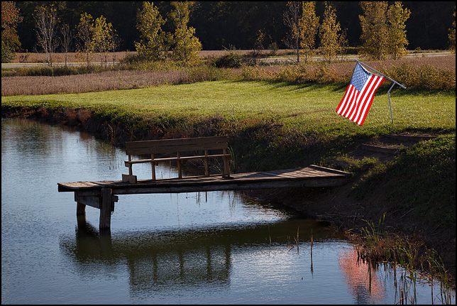 An American flag glows in the late afternoon light next to a pond in rural Wabash County, Indiana. A wooden bench sits on the pier.