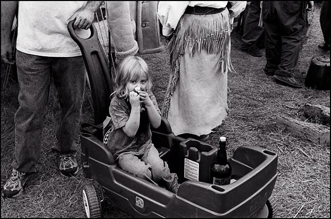 A little blonde girl with a shy look on her face clutches a bottle while her father pulls her in a wagon at the Johnny Appleseed Festival in Fort Wayne, Indiana.