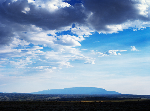Fluffy clouds form in the blue sky over the Sandia Mountains near Albuquerque, New Mexico.