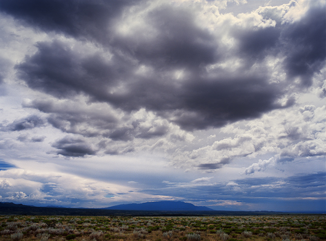 Clouds gather in the big sky of New Mexico with the Sandia Mountains silhouetted in the distance.
