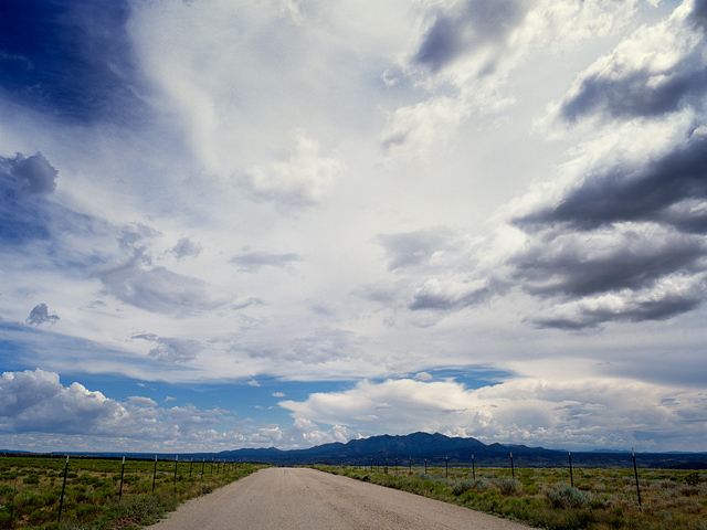 Storm clouds form over Waldo Canyon Road on LaBajada Mesa in Santa Fe County, New Mexico. The jagged peaks of the Ortiz Mountains can be seen in the distance.