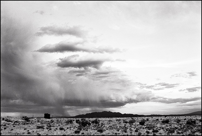 A tall thunderhead gathers strength in the big sky above the Ortiz Mountains in New Mexico.