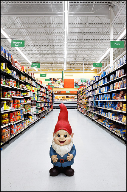 A large three foot tall garden gnome standing in the middle of the pasta aisle in the grocery department of a Walmart store.