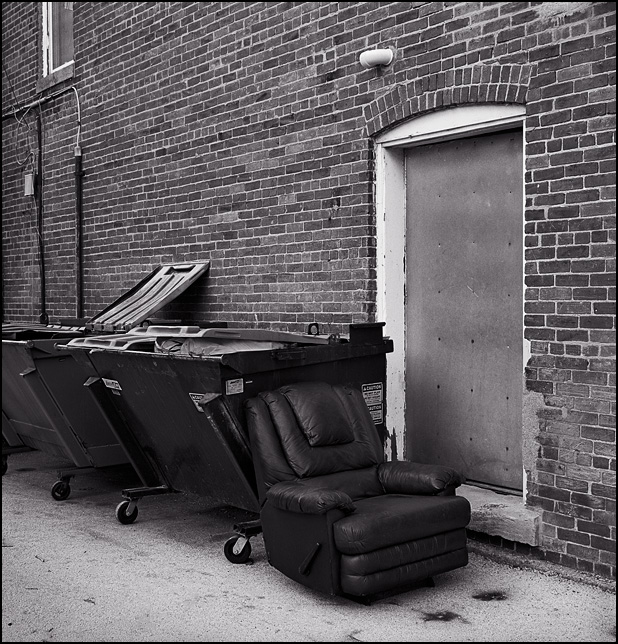 A leather recliner sits next to a couple of dumpsters in an alley next to an old brick building in the small town of Wapakoneta, Ohio.
