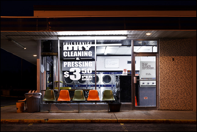 A row of chairs sit on the sidewalk in front of the brightly lit store window next to The Wash House Laundry and Dry Cleaning on South Calhoun Street in Fort Wayne, Indiana.
