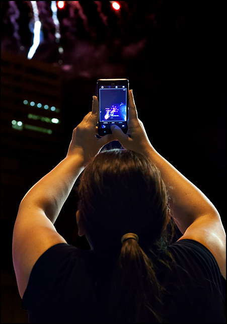 A woman holding up her smartphone at the 2017 Fourth of July Fireworks in Fort Wayne, Indiana. She is watching the fireworks on the screen.