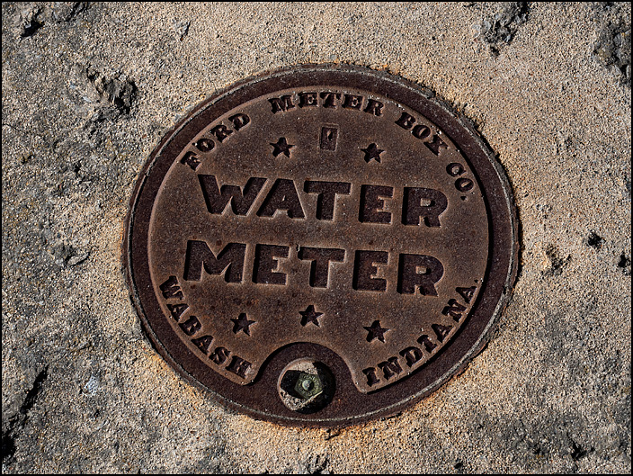 A cast iron water meter cover made by the Ford Meter Box Company in Wabash, Indiana. The meter box is set into a sidewalk on Marion Street in the small town of Waterloo, Indiana.