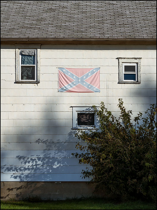 A faded Confederate flag hangs on the side of an old white house with peeling paint on Wayne Street in the small town of Waterloo, Indiana.