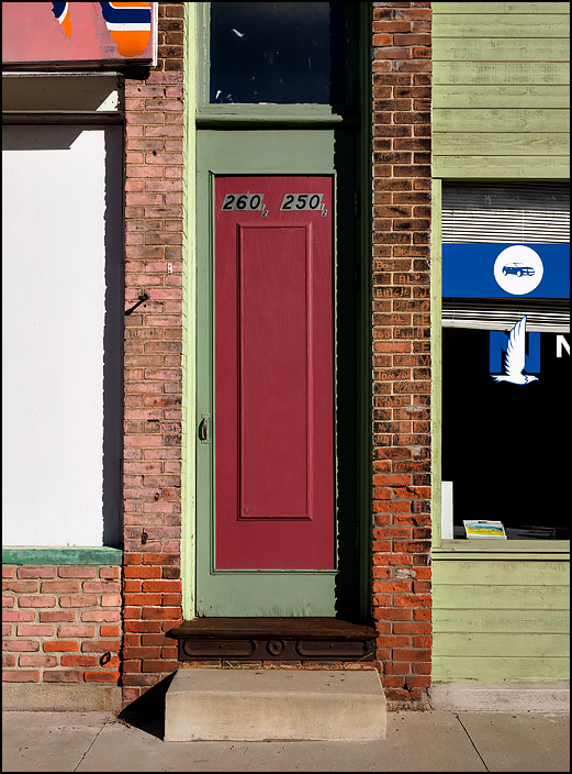 An apartment door on the front of an old brick commercial storefront building on Wayne Street in the small town of Waterloo, Indiana. The door leads to an apartment on the second floor of the building.