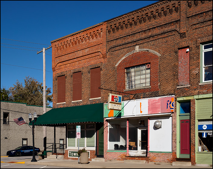 A row of old brick commercial storefront buildings on Wayne Street in the small town of Waterloo, Indiana. The former Town Hall building, Charitos Mexican Buffet, and Baker Insurance are pictured.