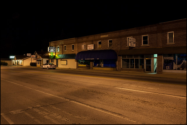 A night photograph of the main business district of Waynedale on Lower Huntington Road in Fort Wayne, Indiana. The Elzey building with the Waynedale Bakery, Hook and Ladder Tavern, and Meyers Barbershop are visible along the road.