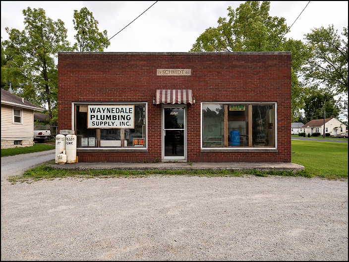 The front of Waynedale Plumbing Supply on Lower Huntington Road in Fort Wayne, Indiana. It is a small brick building with three propane tanks sitting on the sidewalk in front of the store.