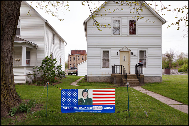 An American flag banner in the front yard of a house on West Main Street in Fort Wayne, Indiana. The banner has a photo of army veteran Laura Bonano and the message, Welcome Home From Afghanistan Laura.