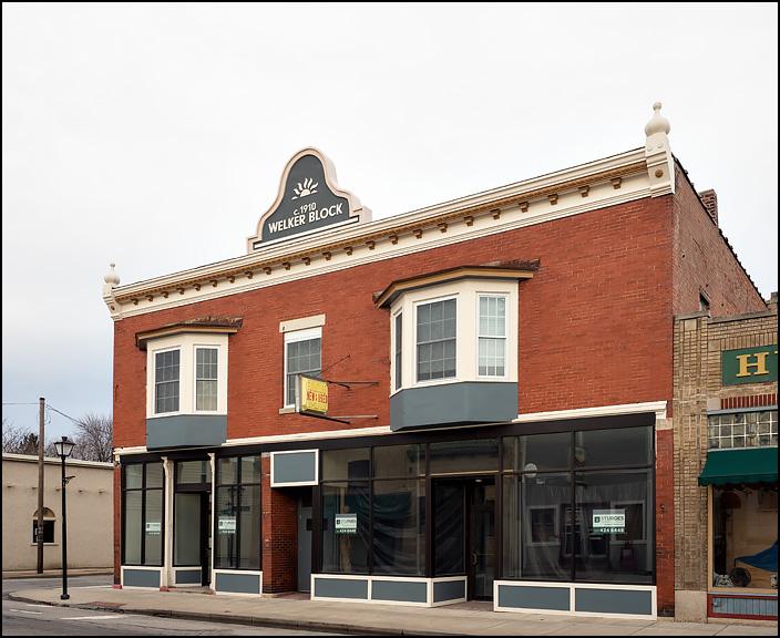 The Welker Block, a historic brick commercial building on the corner of Wells Street and Fourth Street in Fort Wayne, Indiana. There are two storefronts on the first floor and apartments with bay windows on the second floor.