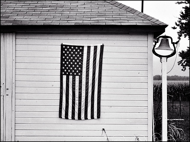An American flag hangs next to an old school bell on the front of the garage behind a farmhouse on State Road 1 in Wells County, Indiana.