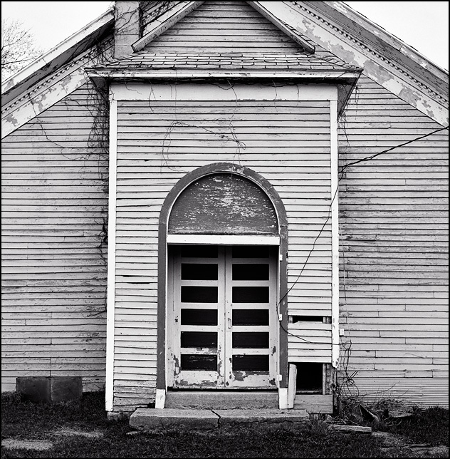 The front doors of an abandoned wood-frame church on County Road 100E in Wells County, Indiana.