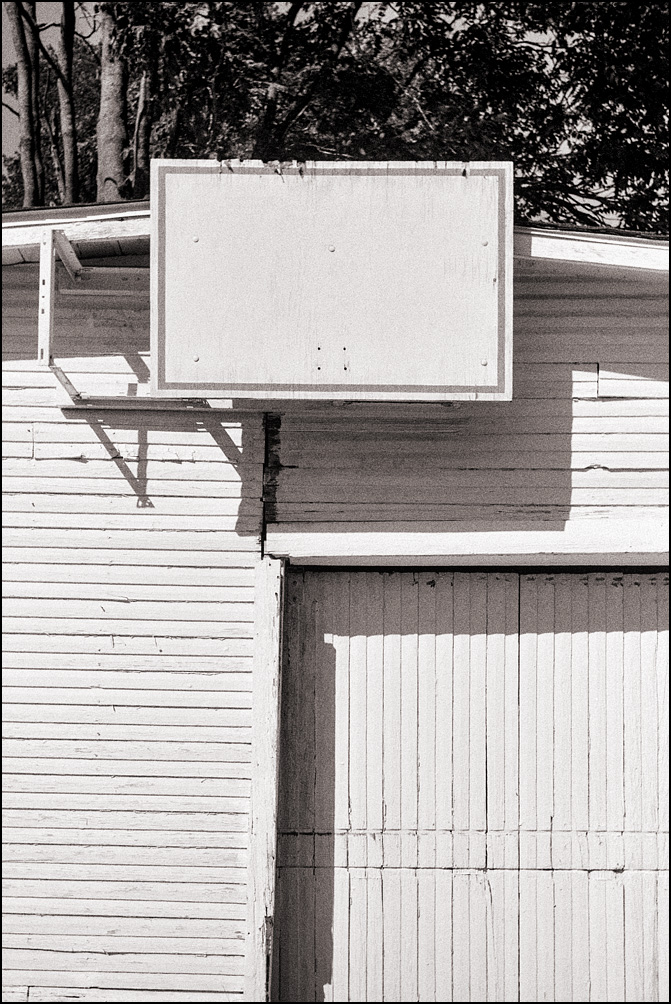 An old garage behind a house on Wells Street in Fort Wayne, Indiana. There is a basketball backboard with no hoop hanging over the door.