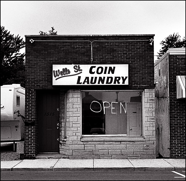 The open sign painted on the front window of the Wells Street Coin Laundry in Fort Wayne, Indiana.
