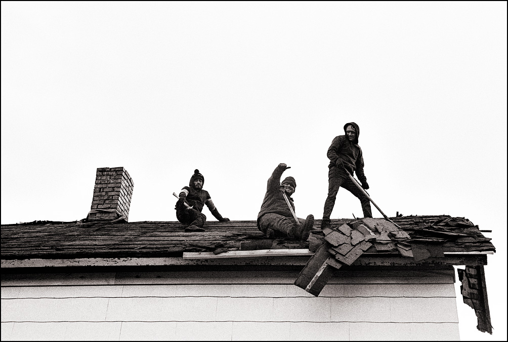 A group of roofers working on an old house on Wells Street in Fort Wayne, Indiana. One of the men is giving a thumbs-up.