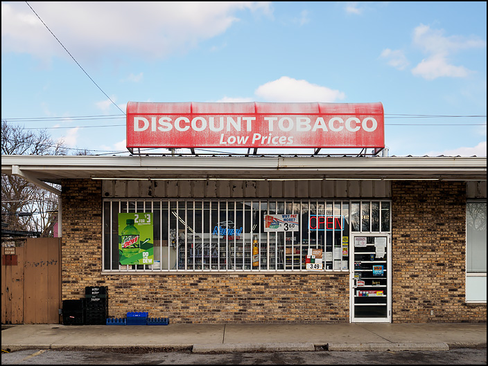 A discount tobacco store on Wells Street in Fort Wayne, Indiana. The windows have steel bars and are filled with signs advertising cigarettes, beer, and soda pop.