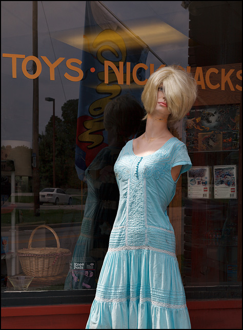 A blonde armless mannequin wearing a blue dress stands in front of Wells Street Variety Store in Fort Wayne, Indiana. Lettering on the window behind her says Toys and Knick Knacks.