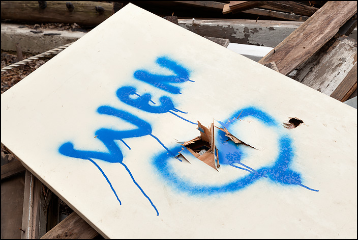 A door on a pile of debris during the demolition of an old farmhouse on Lower Huntington Road in rural Allen County, Indiana. There is graffiti on the door of a heart and the word When, misspelled as Wen.