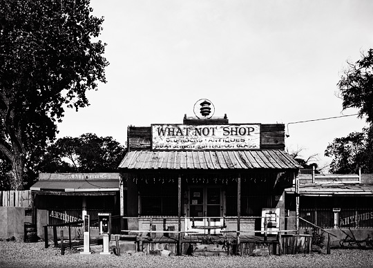 The What Not Shop in Cerrillos, New Mexico looks like an old west saloon building with a porch and false front. An old cigarette machine sits on the porch and a pay phone stands in front of the store.