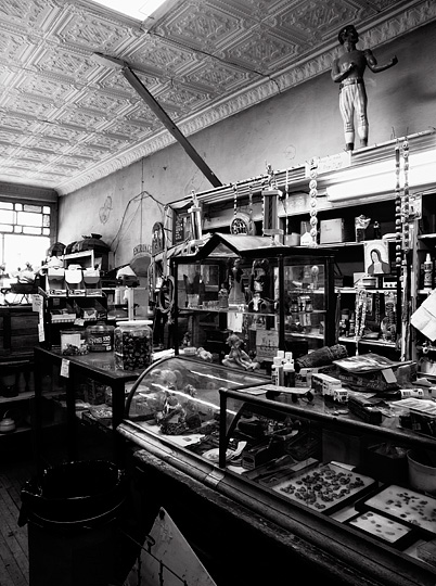 The display cases and counter inside the What Not Shop in Cerrillos, New Mexico. The shop looks like an old west store with an old fashioned tin ceiling and stained glass in the front windows. The old wooden display cases are overfilled with antiques, rocks, and junk. A statue of a nineteenth century boxer stands over a display case full of Indian jewelry and pictures of the Virgin Mary.