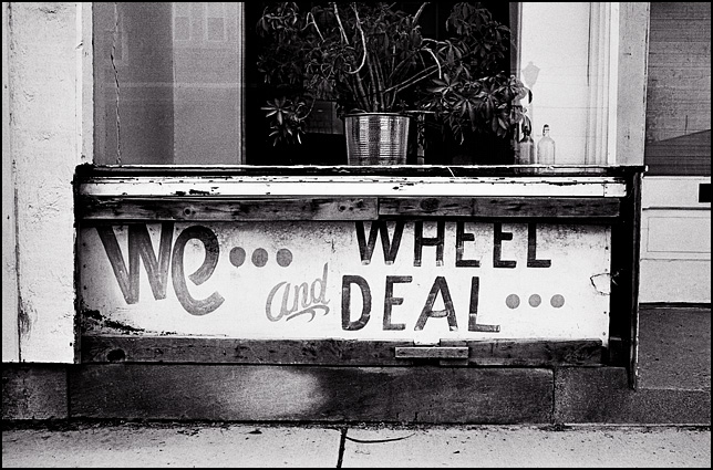 We Wheel and Deal sign on an abandoned storefront on Wells Street in Fort Wayne, Indiana.