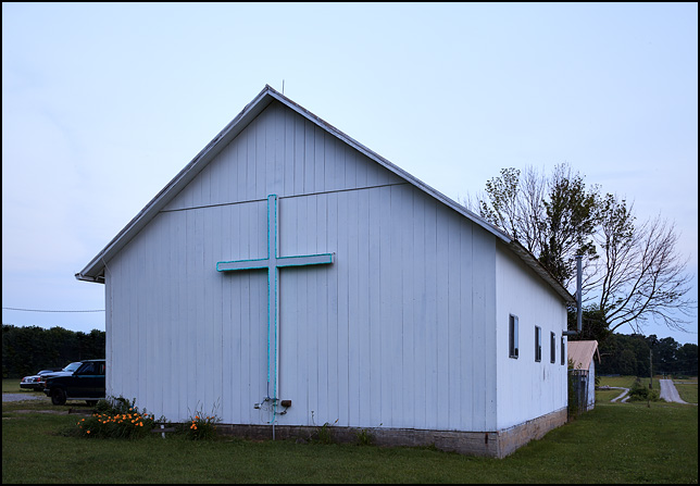 A small white barn at sunset with a large cross lit up with blue Christmas lights.