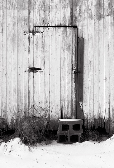 Snow on the ground around the door of a white abandoned barn in rural northwest Allen County, Indiana. The door is held shut by a stack of cinderblocks.