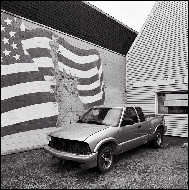 A wrecked Chevrolet S-10 pickup truck sits in front of a faded and peeling mural of the Statue of Liberty and an American Flag in Fort Wayne, Indiana.