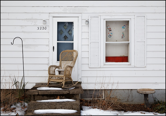 A wicker rocking chair sits on the tiny front step of a house on Sandhill Drive in Fort Wayne, Indiana. A bird feeder sits on the chair and a concrete birdbath stands in front of the house under the window.