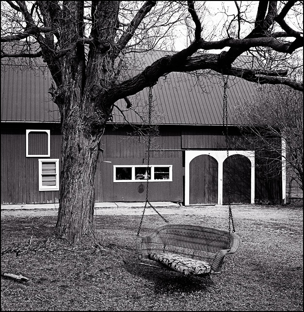 A wicker porch swing hangs from a tree in front of an old barn at the Horney Robinson Farm on Lower Huntington Road in Allen County, Indiana.