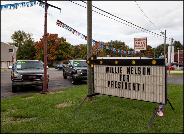 A flashing arrow sign that says, Willie Nelson For President. The sign is in front of Southside Auto Sales on Bluffton Road in the Waynedale area of Fort Wayne, Indiana.