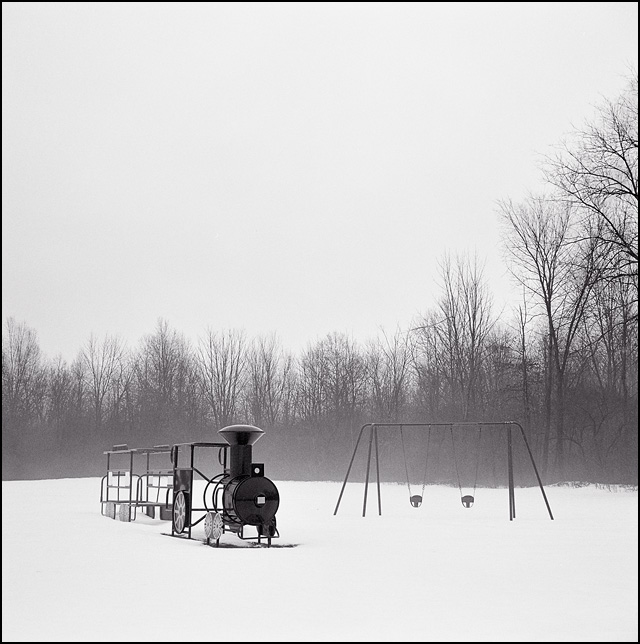 A swing set and a jungle gym shaped like a train sit in the snow on a rainy foggy winter day.