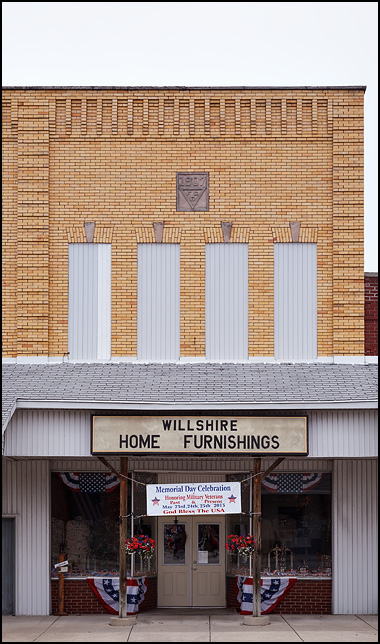 Willshire Home Furnishings, a furniture store in a yellow brick building in the small town of Willshire, Ohio. Patriotic bunting and a Memorial Day decorate the storefront.