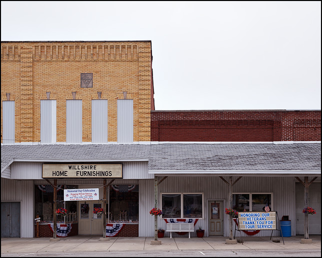 Willshire Home Furnishings, a furniture store in the small town of Willshire, Ohio decorated for Memorial day with American flags and a sign honoring veterans.