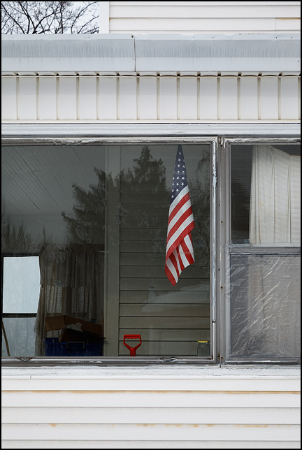 An American flag hangs in the side window of an old house on Wabash Avenue in an inner-city neighborhood in Fort Wayne, Indiana.