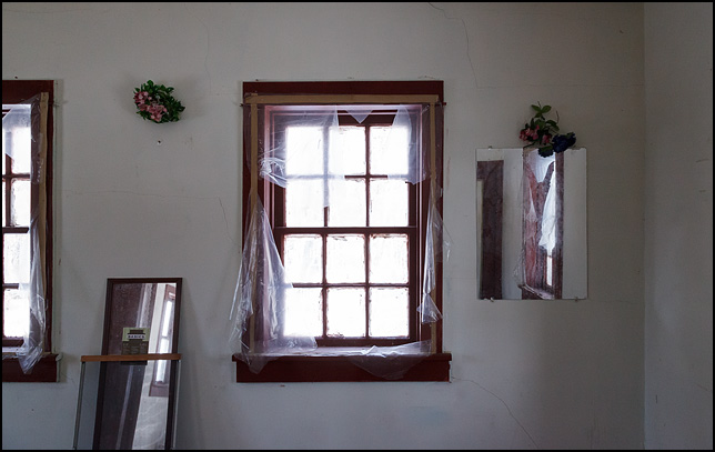 Mirrors and windows in an abandoned house in rural Elkhart County, Indiana. Bouquets of plastic flowers hang on the wall between the windows.