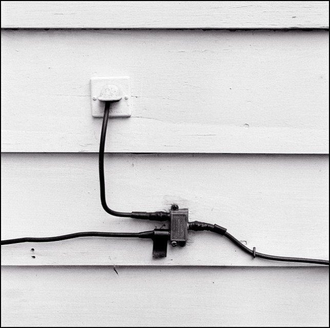 A cable TV splitter and wires stapled to the side of an old white house.