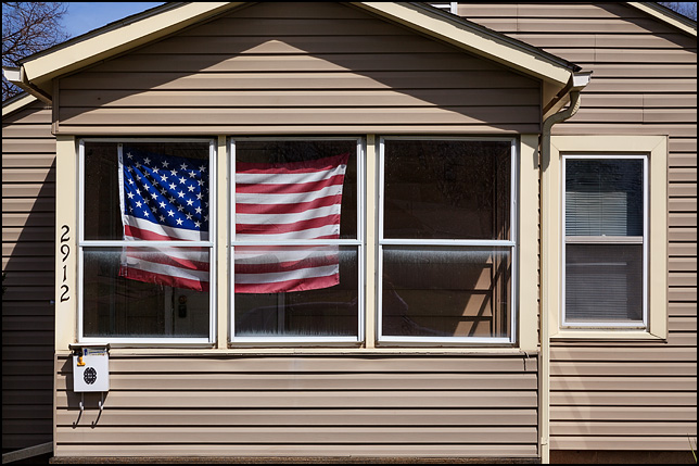 A large American flag in the front window of the enclosed porch of a small house on Witchwood Drive in the Waynedale area of Fort Wayne, Indiana.