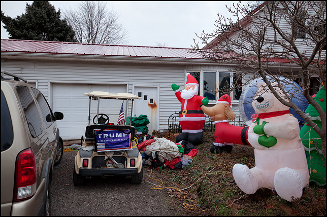 A golf cart with a Trump For President sign sits in the driveway of a house with numerous inflatable Christmas decorations in the front yard. The house is on Main Street in the small town of Wolf Lake, Indiana.