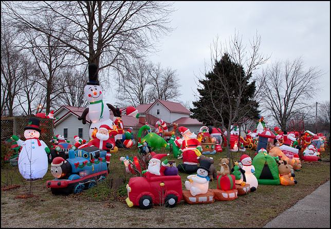 Inflatable Christmas decorations completely fill the back yard and side yard of a house on Main Street in the small town of Wolf Lake, Indiana. Photographed at dusk.