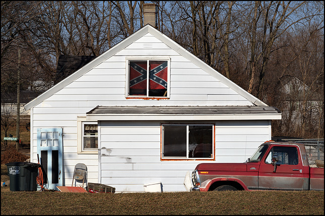 A house with a Confederate flag in the upstairs window and an old Ford pickup truck parked in front. The house is on Main Street in the small town of Wolf Lake, Indiana.