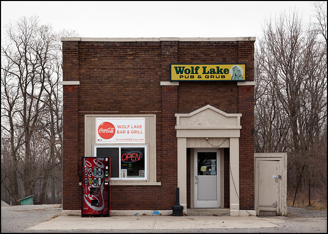 Wolf Lake Pub and Grub is a bar in a small brick building that was originally built as a bank on US-33 in the small town of Wolf Lake, Indiana. A Coke machine stands in front of the building.
