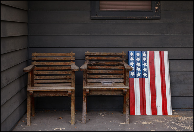 Hand-painted American flag on a piece of old wooden siding next to two wooden chairs on the front porch of a house on Lower Huntington Road in rural Allen County, Indiana.