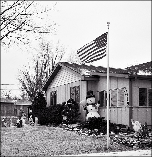 An American flag waves in front of a house decorated with a nativity scene and an inflatable snowman on Christmas day.