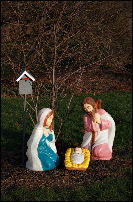 A nativity scene with glowing plastic figures of Mary and Joseph with baby Jesus next to a birdhouse in the front yard of a house on Woodheath Avenue in Fort Wayne, Indiana.
