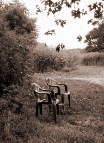 Pinhole photograph of a pair of plastic patio chairs under a tree on a farm in rural Indiana.